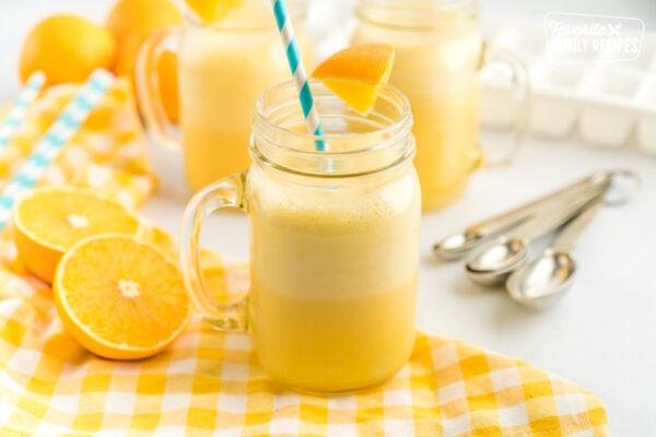 A mug of Orange Julius with a blue straw and an orange slice garnish