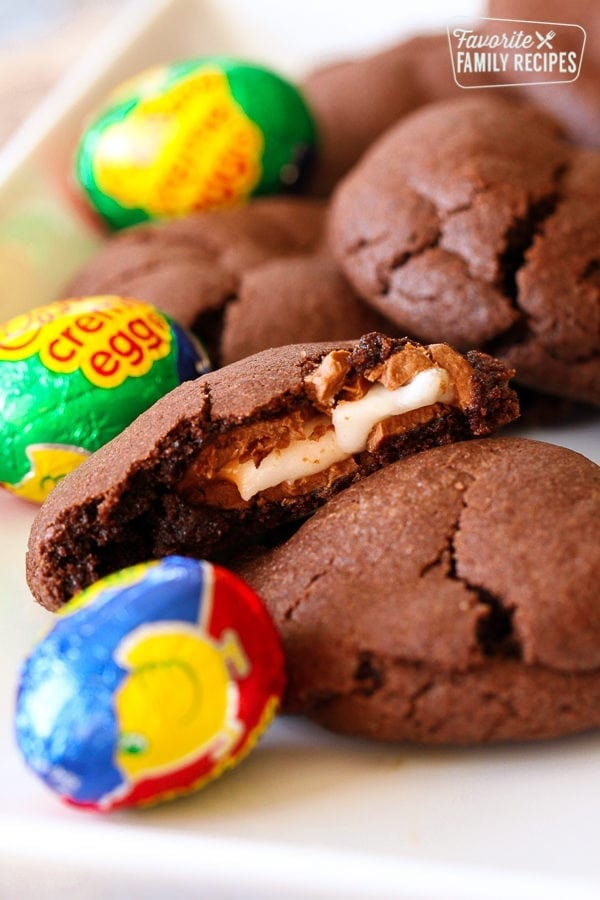 Chocolate Easter Cookies filled with a Cadbury Cream Egg on a plate with Cadbury Creme Egg candies