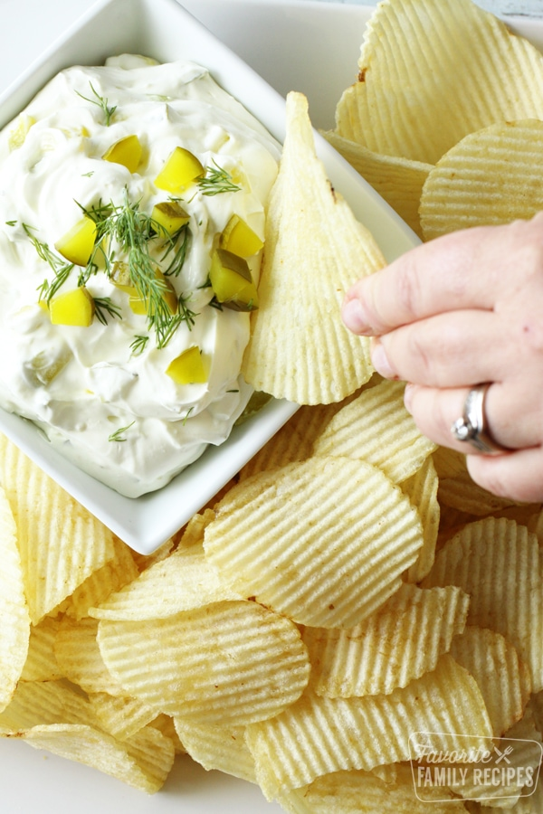 Potato chip being dipped in creamy dill pickle dip