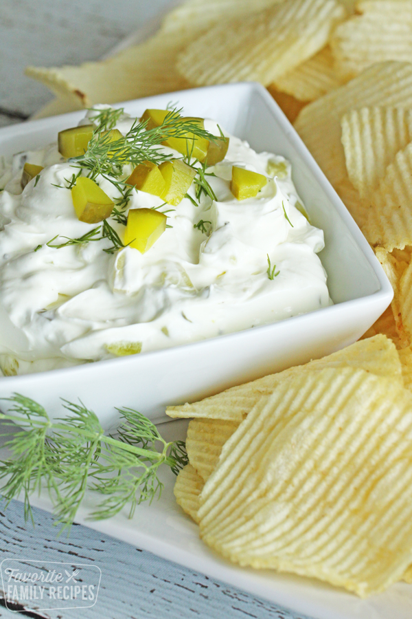 Creamy dill pickle dip topped with chunky dill pickles and fresh dill served with potato chips