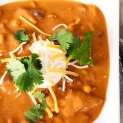 A bowl of Instant Pot Chicken Enchilada soup garnished with sour cream, shredded cheese, and cilantro
