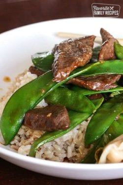 Beef and Snow Peas over rice in a white bowl.