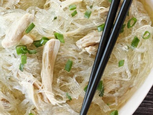 Glass noodles in a bowl with shredded chicken and green onions