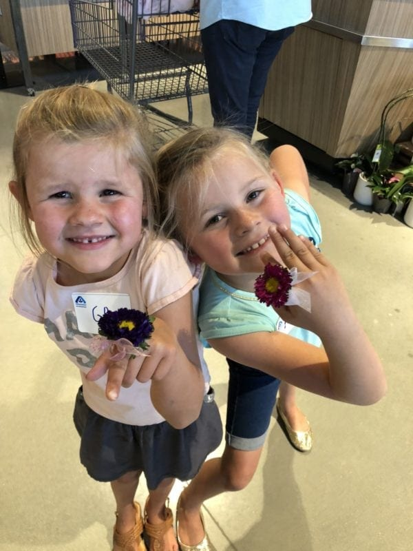 Two young girls smiling with Albertsons fresh flower rings
