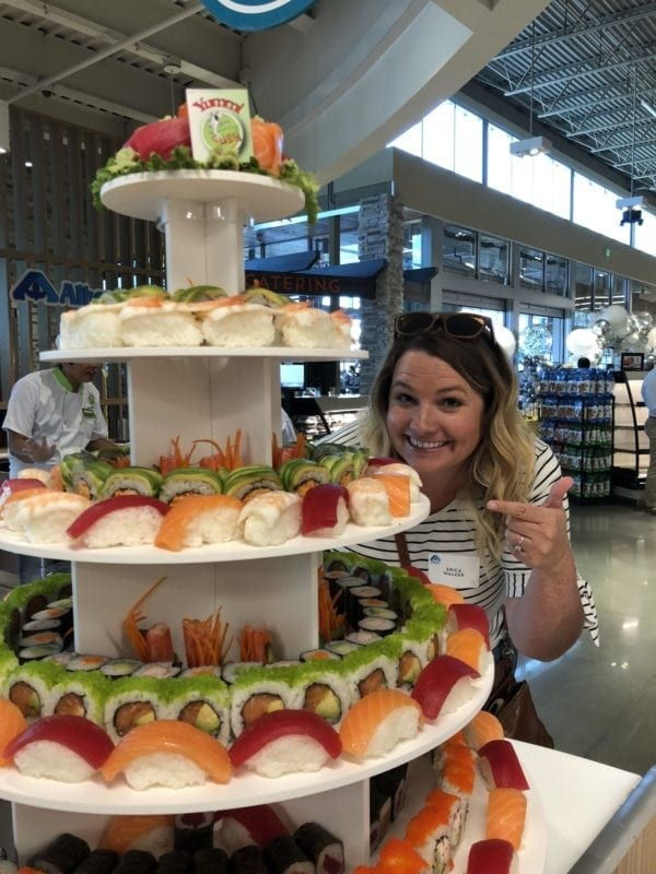 Erica pointing to the Sushi Tower at the Albertsons grand opening in Boise