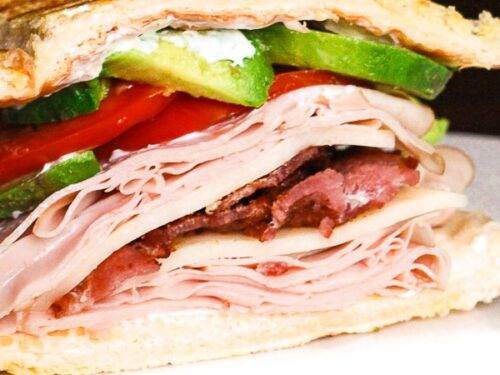Close up of Inside Out Panini Gobbler Sandwich on a white plate.
