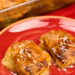 2 Apple Dumplings on a red plate with the pan of dumplings in the background.