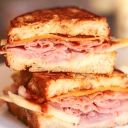 Apple, Ham, and Cheddar Melt Sandwiches stacked on top of each other on a white plate.