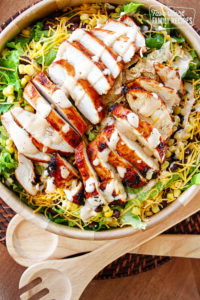 BBQ Chicken Salad with Creamy BBQ Dressing in a wooden bowl with 2 wooden spoons off to the side.