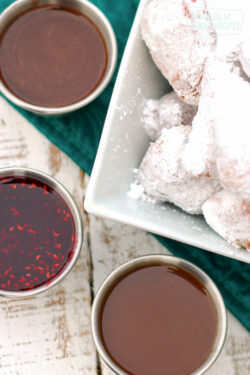 3 dipping sauces in little silver bowls next to a bowl of beignets covered in powdered sugar.