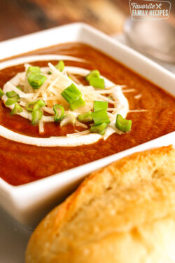 Cafe Zupas Tomato Basil Soup with sour cream, cheese, and green onions in a white bowl