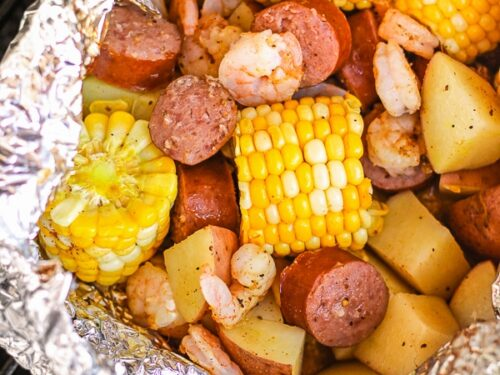 Cajun Shrimp Foil Packets with corn and potatoes on a grill