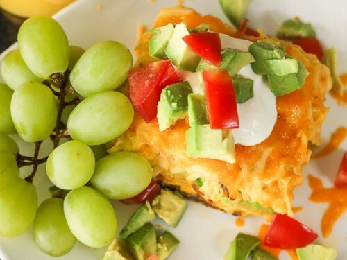A slice of California Breakfast Casserole served with a bunch of green grapes and a glass of orange juice