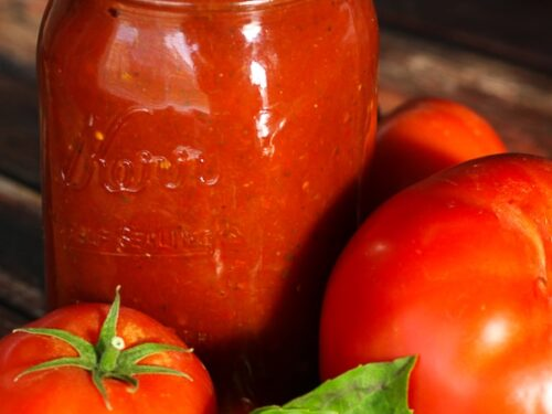 Jar of spaghetti sauce with fresh tomatoes and basil