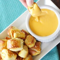 Golden pretzel bites being dipped in cheese