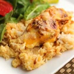 Cheesy Chicken and Rice Casserole with a side salad on a white plate.