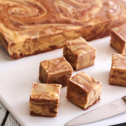 Chocolate Peanut Butter Fudge Swirl slab with cut up pieces on a cutting board