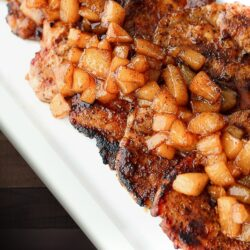 Cinnamon Pork Chops topped with Spiced Pears all on a white tray.
