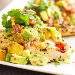 Chicken breast topped with avocado and citrus fruits on a plate Breast Recipe