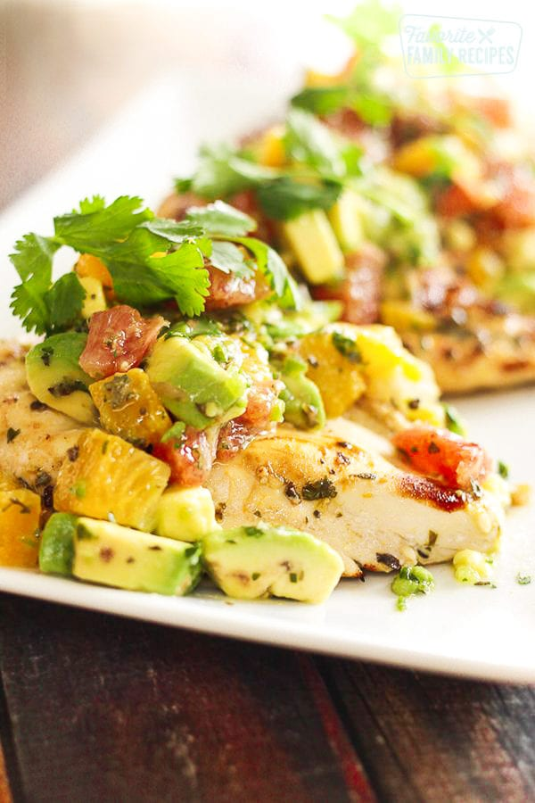 Chicken breast topped with avocado and citrus fruits on a plate