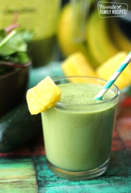 Cool Cucumber Green Smoothie with a slice of pineapple on the rim and a blue straw.