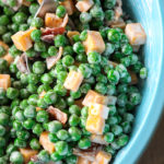 Creamy Green Pea Salad with bacon and cheese being scooped from a turquoise bowl with a serving spoon