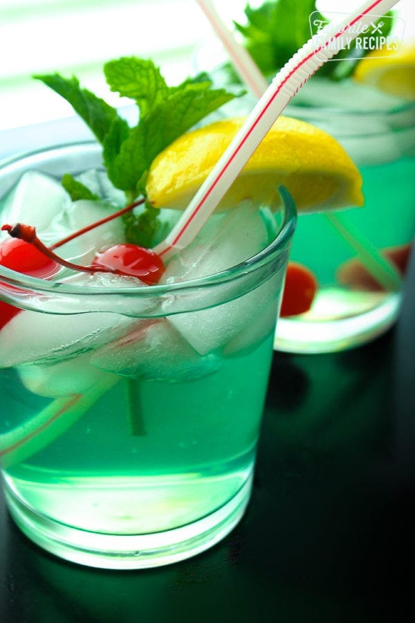 Two Mint Julep drinks served in clear glasses with a lemon slice, maraschino cherries, and a mint leaf for garnish