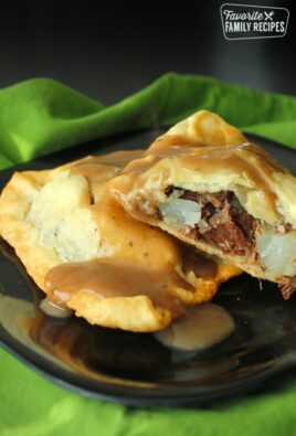 Two Irish Pasties filled with beef and potatoes on a black plate with a green napkin