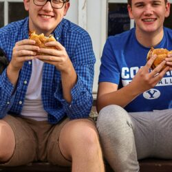 Two teenagers sitting on the back porch eating chicken sandwiches