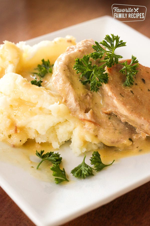 Pork chops made in the Crock Pot on a plate with sauce and mashed potatoes