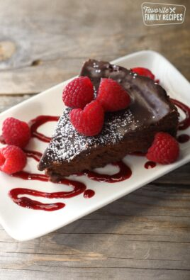 Slice of Easy Flourless Chocolate Cake topped with powdered sugar and raspberries.