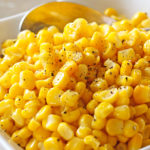 Perfectly cooked frozen corn sprinkled with pepper in a white serving bowl