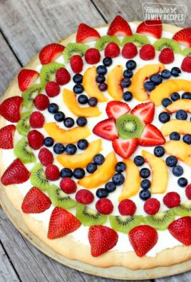 Easy Fruit Pizza decorated with strawberries, kiwi, raspberries, blueberries, and peach slices