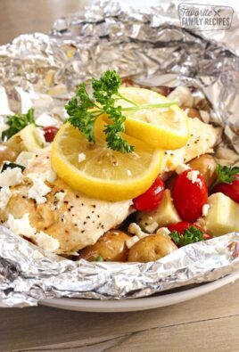 Greek Lemon Chicken Foil Packets with Vegetables and lemon slices topped with a garnish