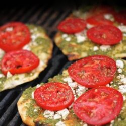 3 Grilled Pesto Pizzas topped with tomatoes on a grill
