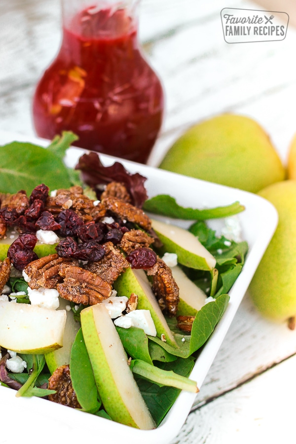 Harvest Pear Salad in a white bowl with Cranberry Vinaigrette Dressing and pears on the side.