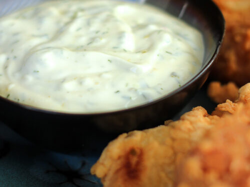 Homemade Tartar Sauce in a black bowl with fish on the side.