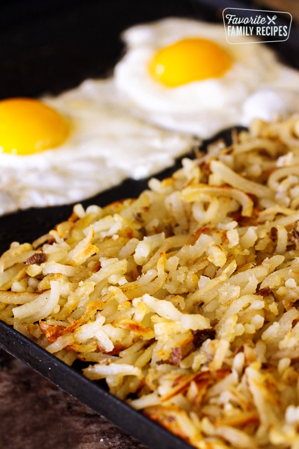 Hash browns served on a cast iron skillet with two fried eggs on the side