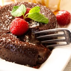 A fork cutting into an Instant Pot Lava Cake topped with raspberries and mint
