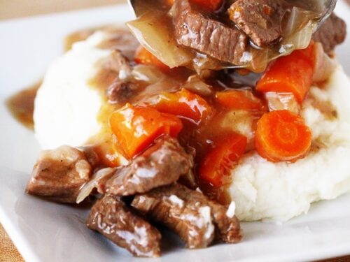 Instant Pot Beef Goulash poured over mashed potatoes on a white plate.