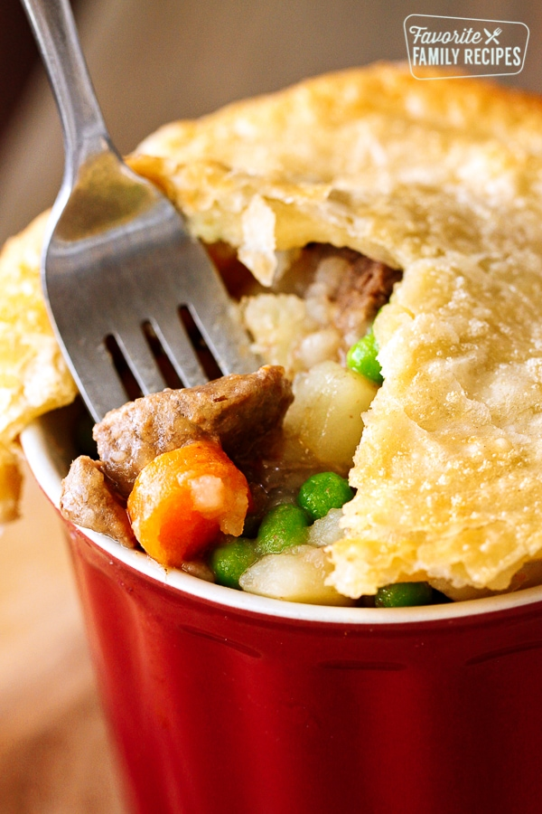 A red dish filled with Instant Pot Beef Pot Pie with chunks of beef, carrots, potatoes and peas