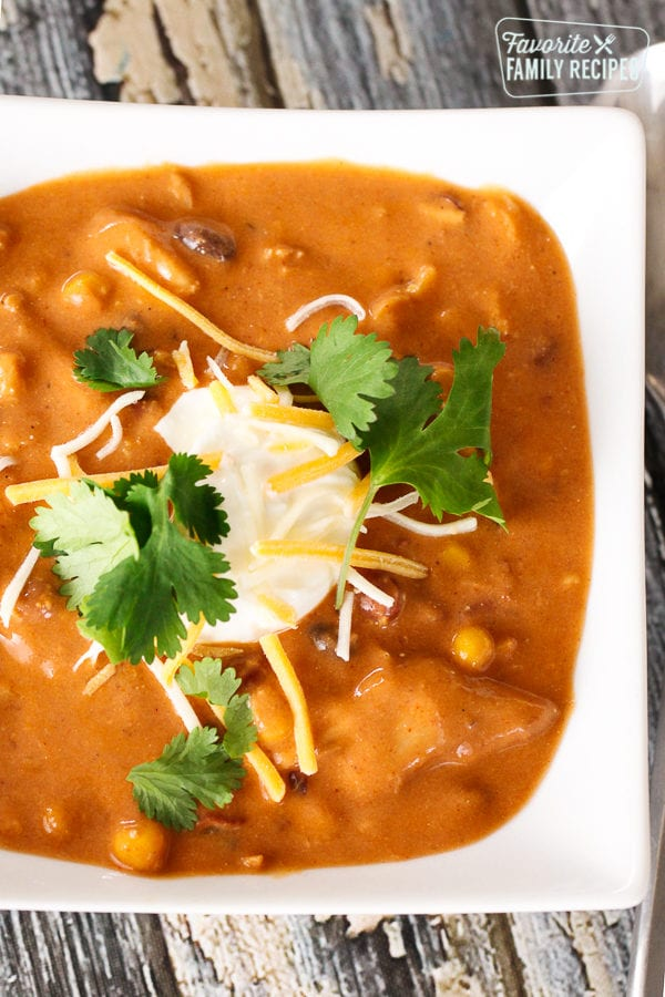 Instant Pot Chicken Enchilada Soup in a white bowl topped with sour cream and cilantro.