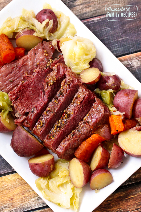 A white tray filled with sliced Instant Pot Corned Beef and Cabbage garnished with red potatoes and carrots