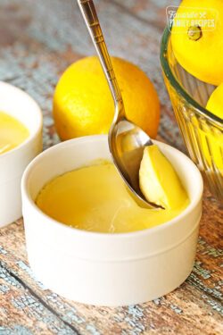 Instant Pot Lemon Custard being scooped from a white custard dish with a spoon
