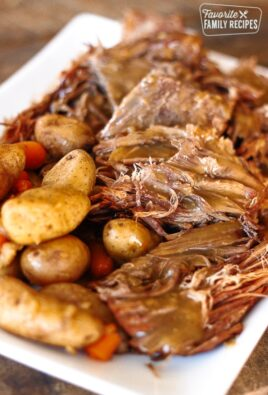 Instant Pot Sunday Beef Roast shredded on a serving plate with potatoes and carrots