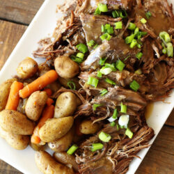 Overhead shot of Instant Pot Sunday Beef Roast shredded on a serving plate with potatoes and carrots