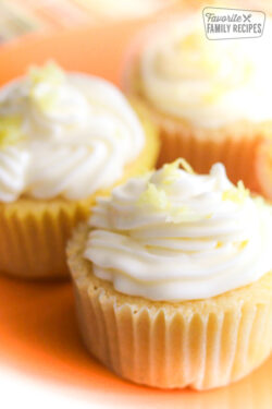 Three Lemon Buttermilk Cupcakes with white frosting and lemon zest on top