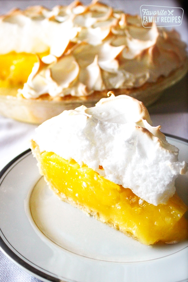Slice of Lemon Meringue Pie on a plate with a full lemon meringue pie in the background