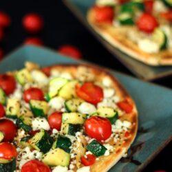 2 mediterranean flatbread pizzas on blue plates