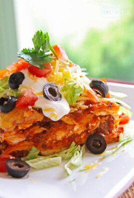 A slice of Mexican Lasagna topped with cheese, olives, lettuce, and cilantro on a white plate.